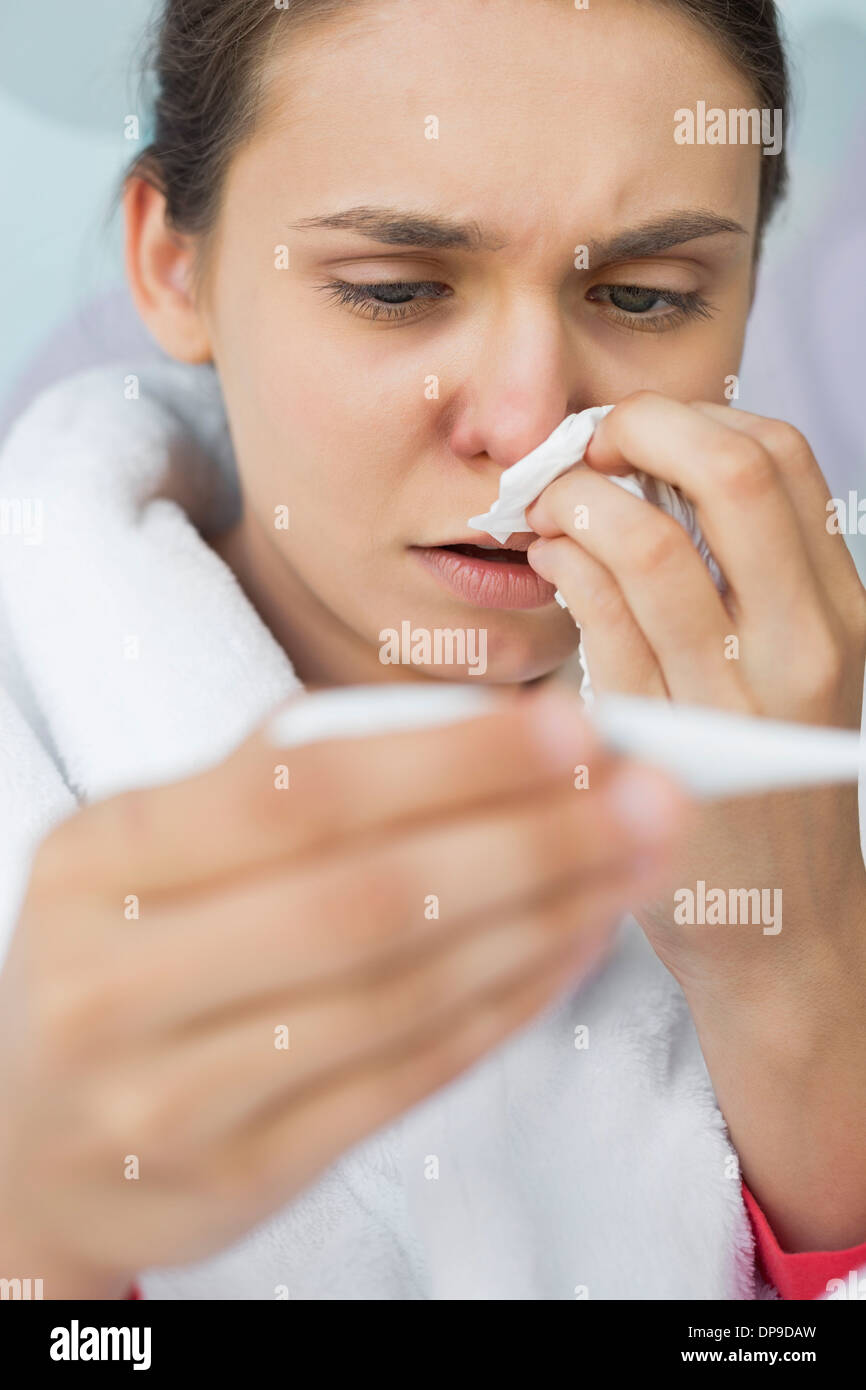 Close-up of worried woman taking her temperature - Stock Image