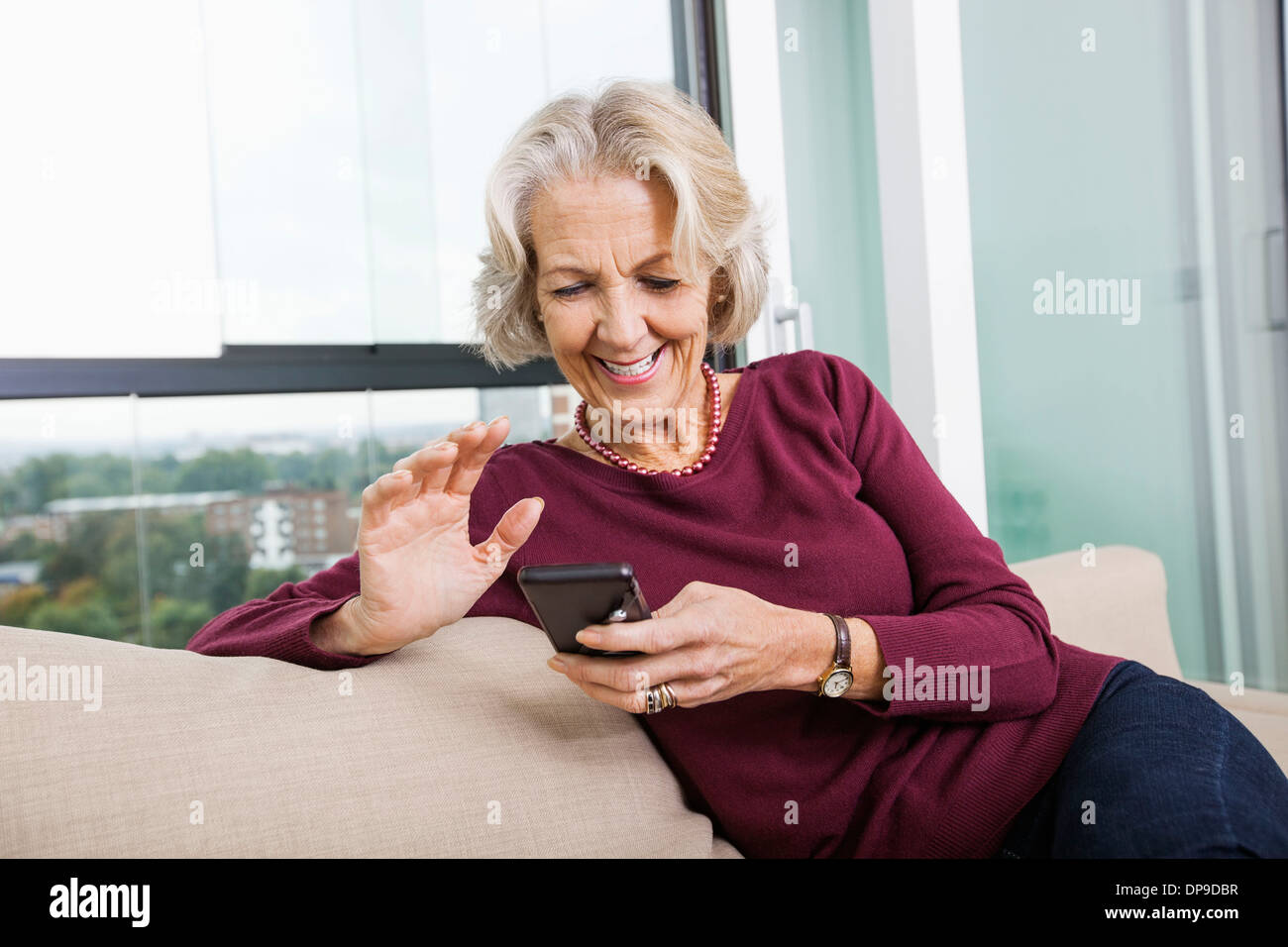 Happy senior woman text messaging through smart phone on sofa at home - Stock Image