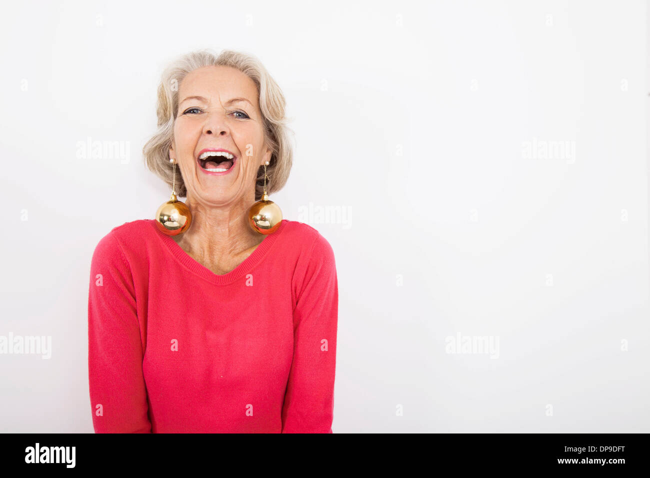 Portrait of senior woman wearing Christmas ornaments over white background - Stock Image