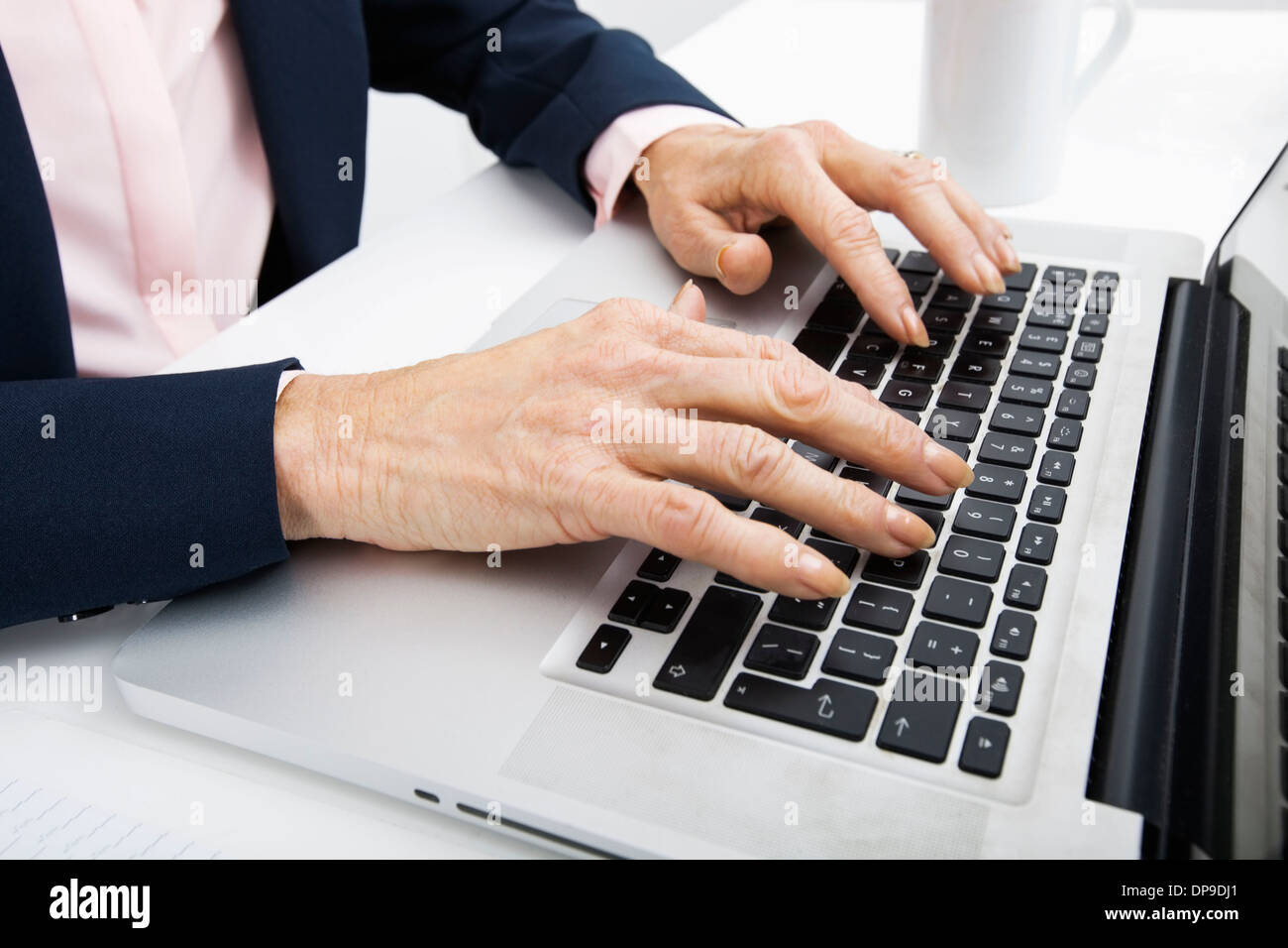 Cropped image of senior businesswoman typing on laptop - Stock Image