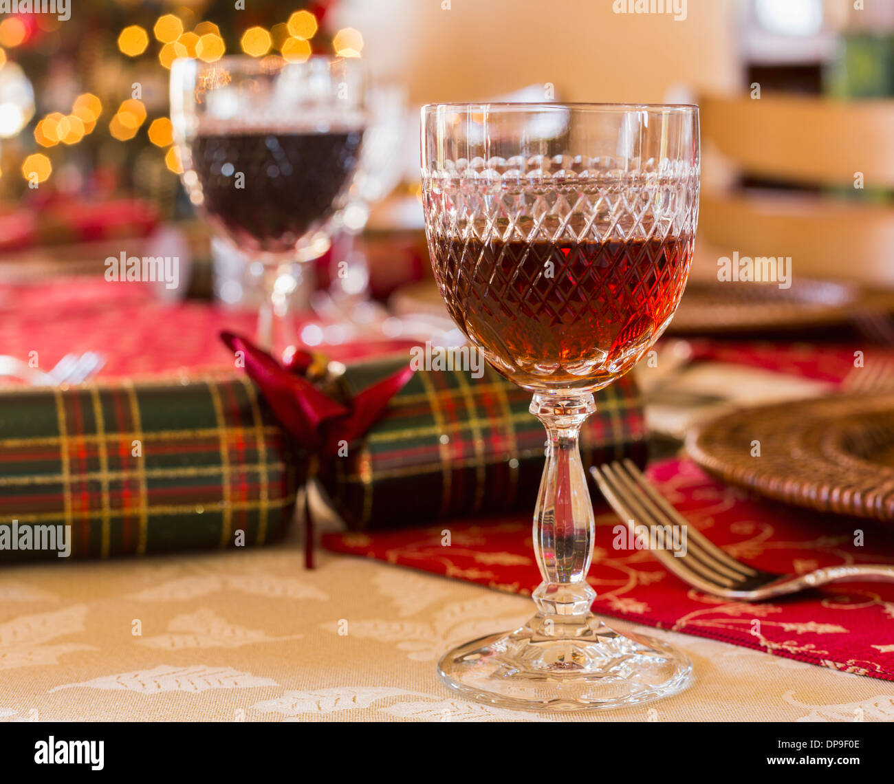 Glass of sherry on a table set for Christmas lunch with crackers and decorated tree in background Stock Photo