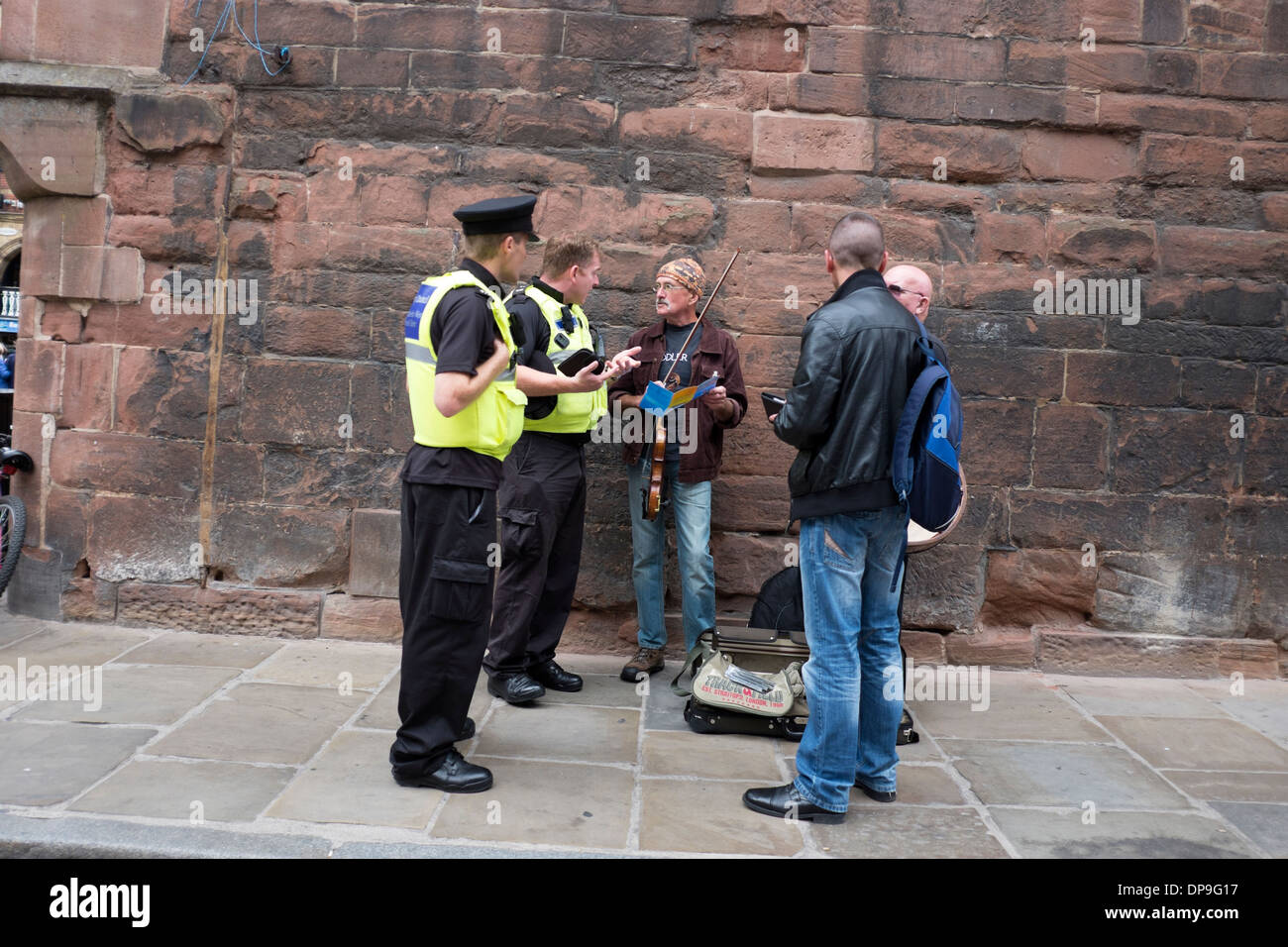 Policemen talking with buskers street entertainers - Stock Image