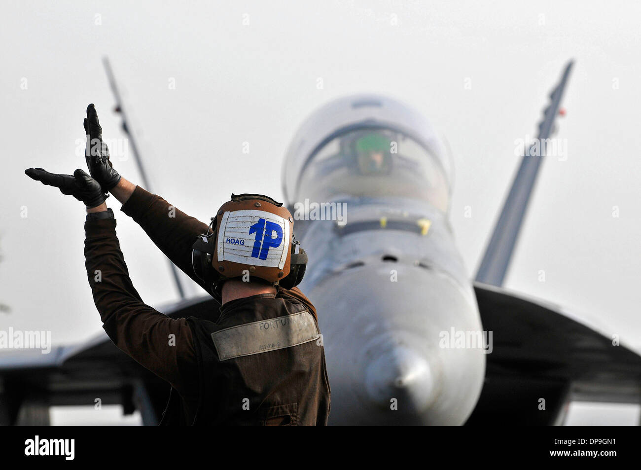 U.S. Navy Airman signals to the pilot of an F/A-18F Super Hornet aircraft - Stock Image