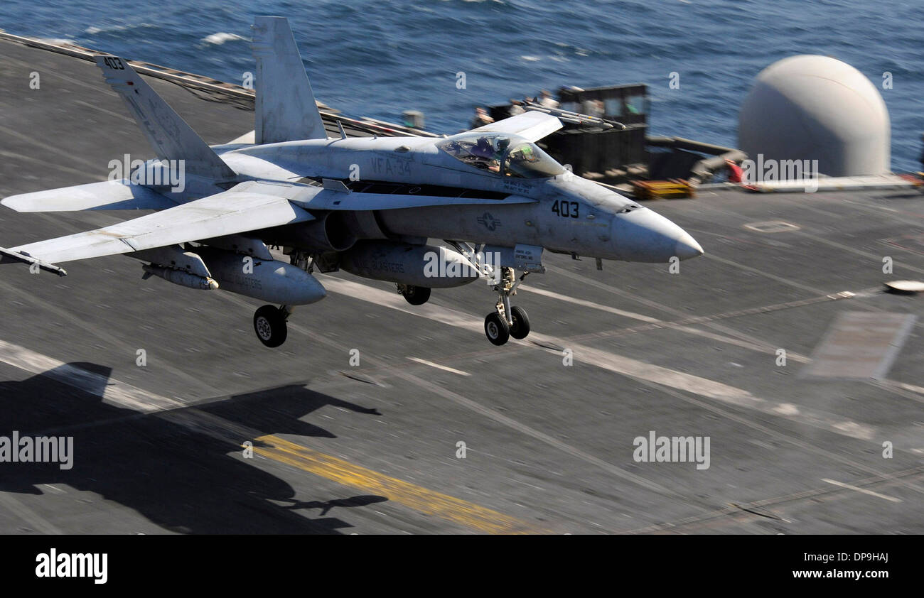U.S. Navy F/A-18C Hornet aircraft lands aboard the aircraft carrier USS Abraham Lincoln - Stock Image