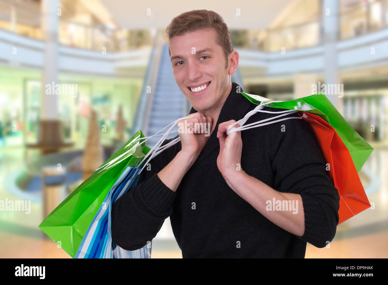 Smiling young man shopping or buying in a store or mall - Stock Image