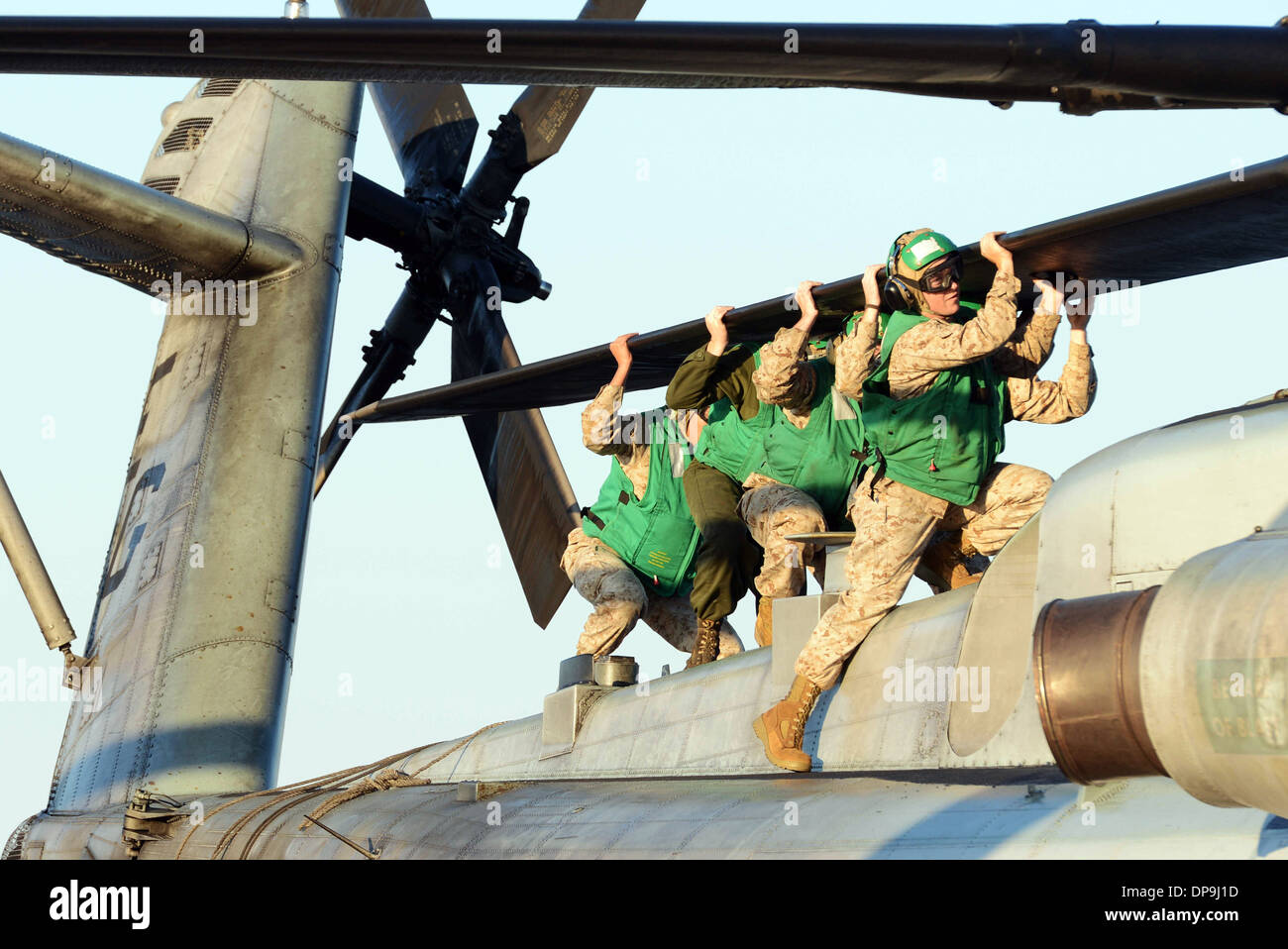 U.S. Marines align the rotor blades of a CH-53E Super Stallion helicopter for stowage - Stock Image