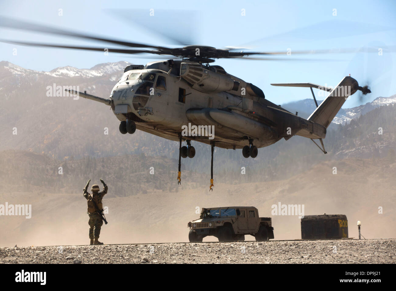U.S. Marine directs the pilots of a CH-53E Super Stallion helicopter after releasing a Humvee Stock Photo