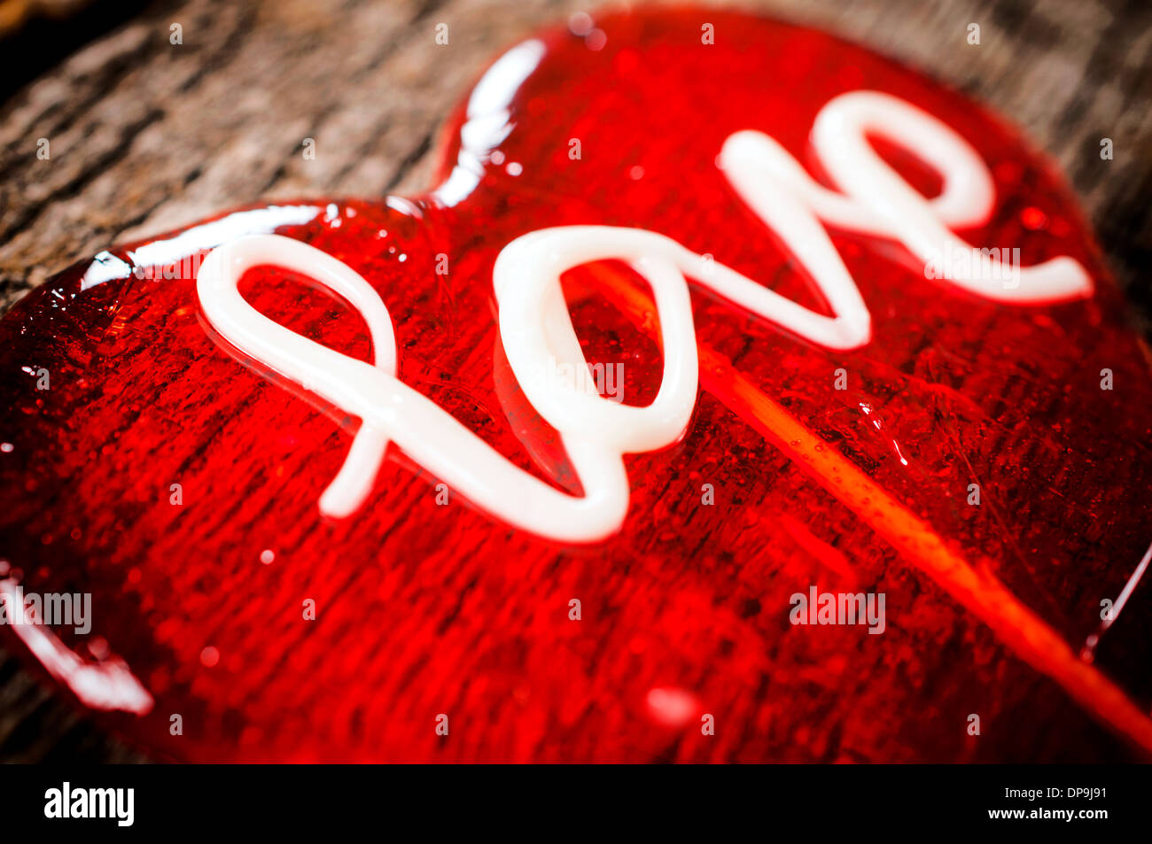 Selective focus on the letter L on heart shape lolly pop - Stock Image