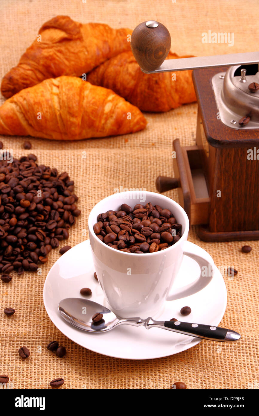 Coffee grain in white cup and croissant, vertical - Stock Image