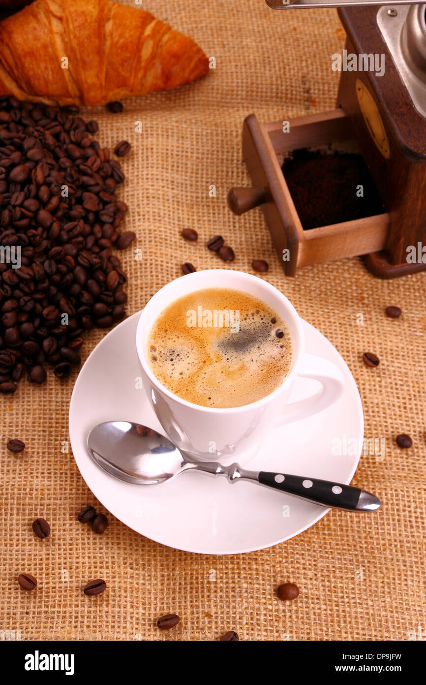 Coffee in white cup, croissant and coffee mill, top view - Stock Image