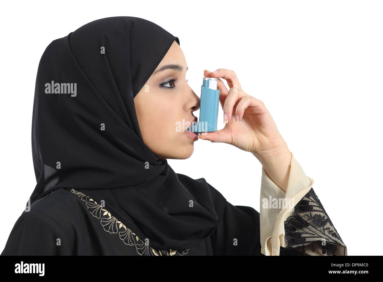 Saudi arabian asthmatic woman breathing from an asthma inhaler isolated on a white background - Stock Image