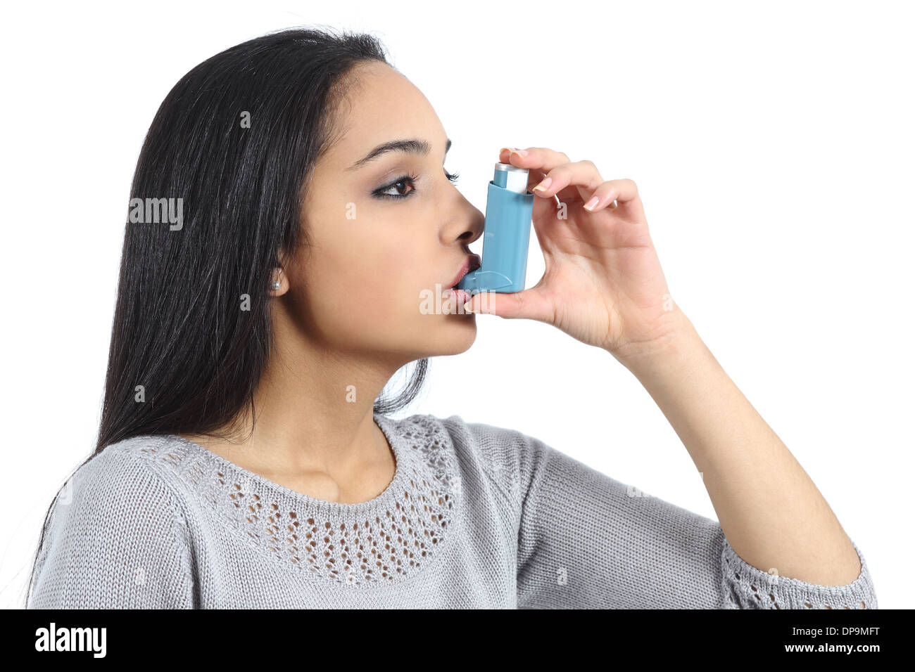 Asthmatic arab woman breathing from a inhaler isolated on a white background - Stock Image
