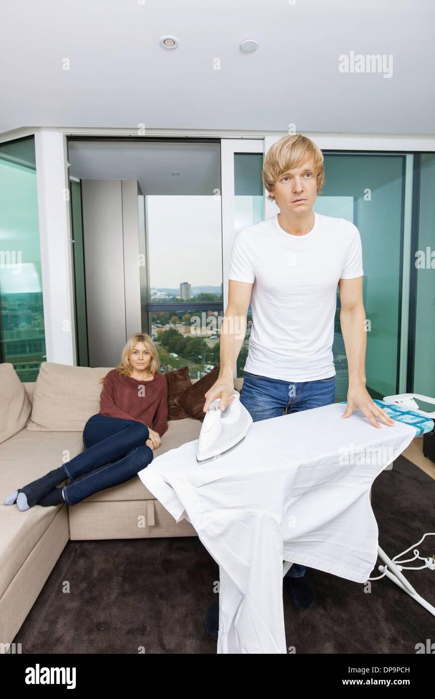 Man ironing shirt while woman sitting on sofa at home - Stock Image