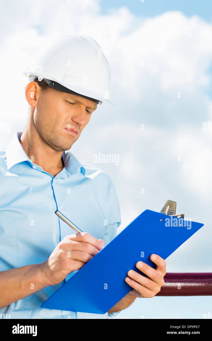 Male architect writing on clipboard against cloudy sky - Stock Image