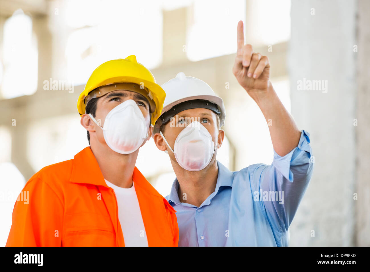 Male architects wearing protective mask while working at construction site - Stock Image