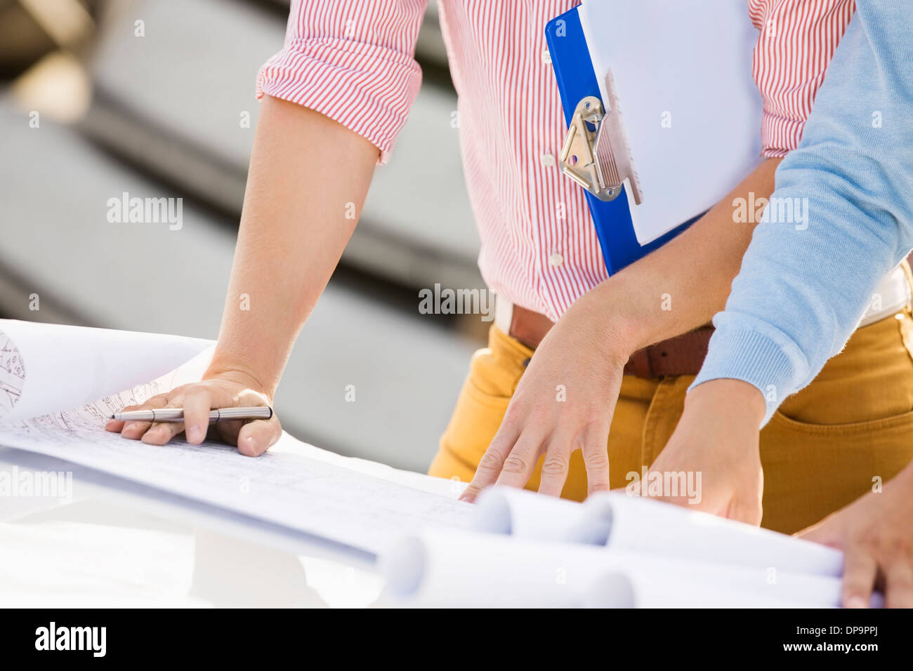 Cropped image of architects with blueprints and clipboard - Stock Image
