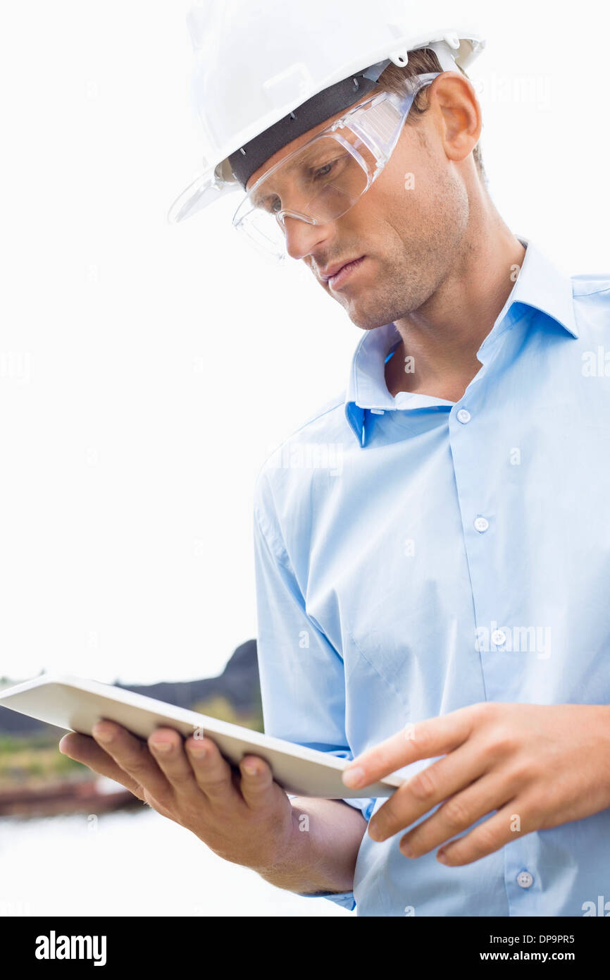 Male architect looking at tablet PC against sky - Stock Image