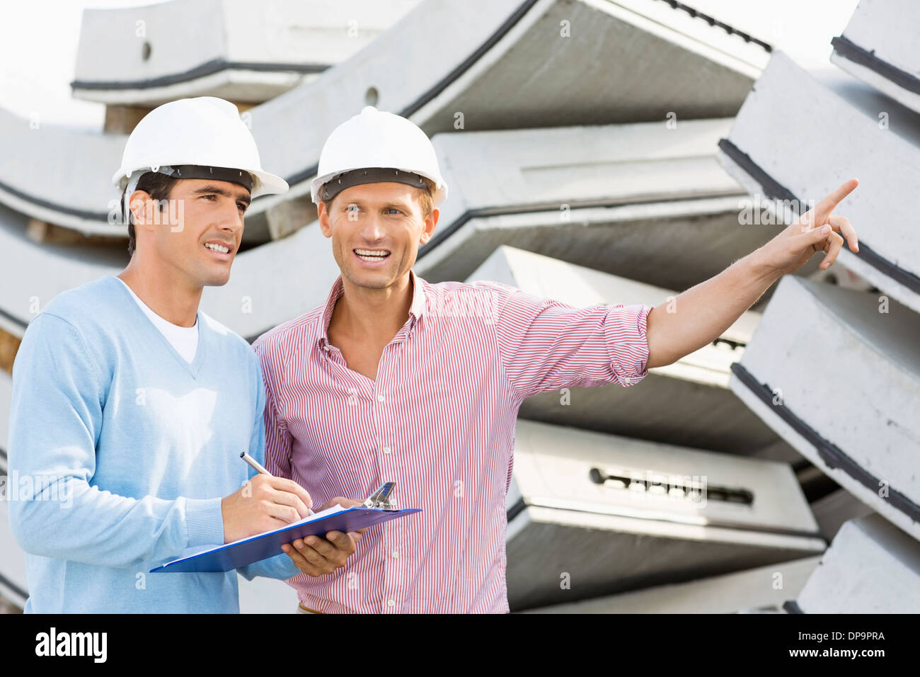 Smiling architects inspecting stock at site - Stock Image