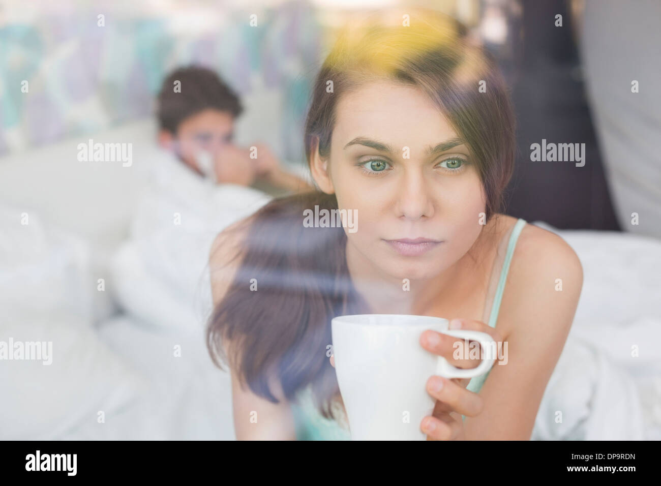 Thougtful woman having coffee at home with man lying in background - Stock Image