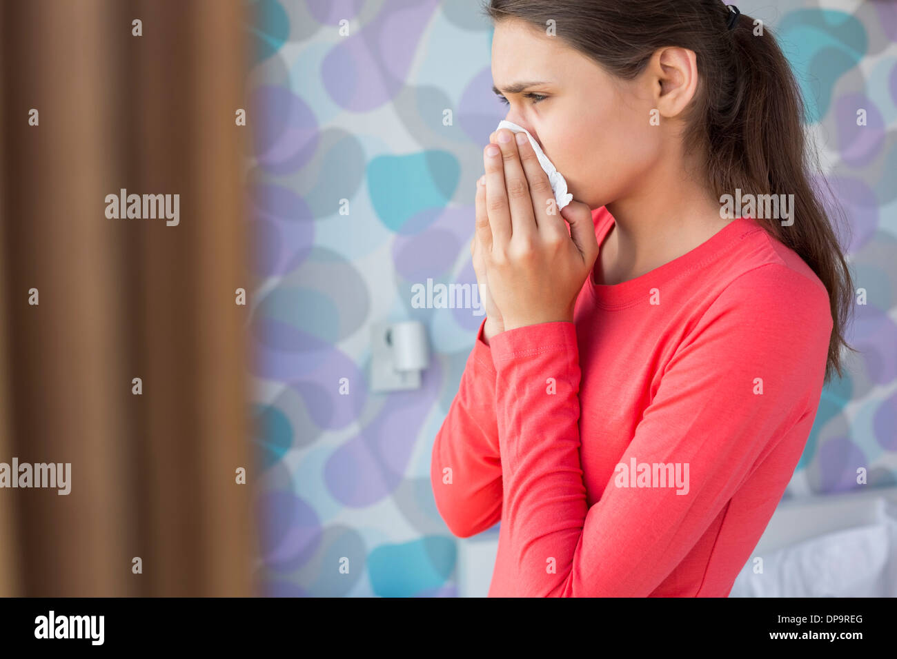 Side view of young woman blowing nose at home - Stock Image