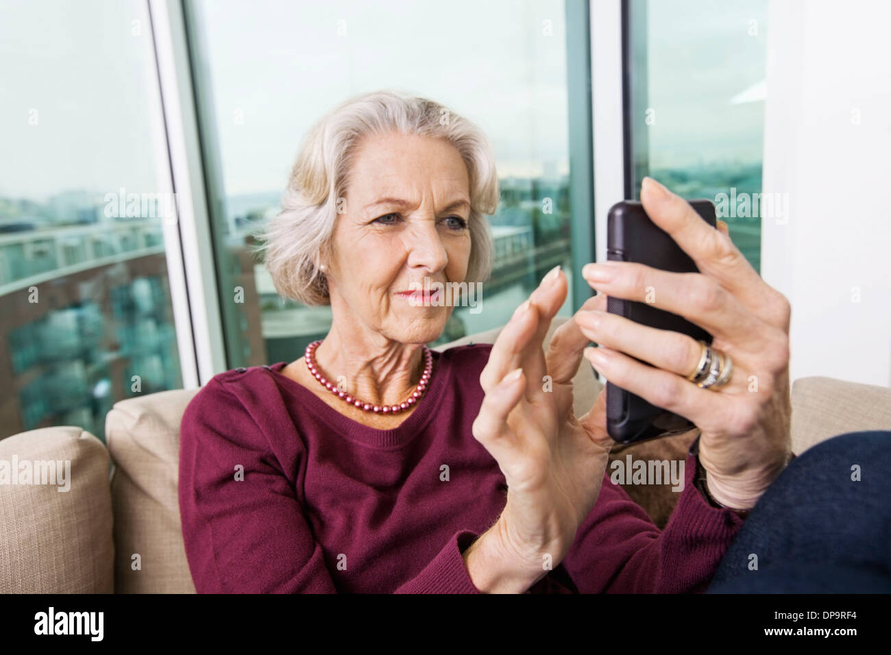 Smiling senior woman text messaging on smart phone at home - Stock Image