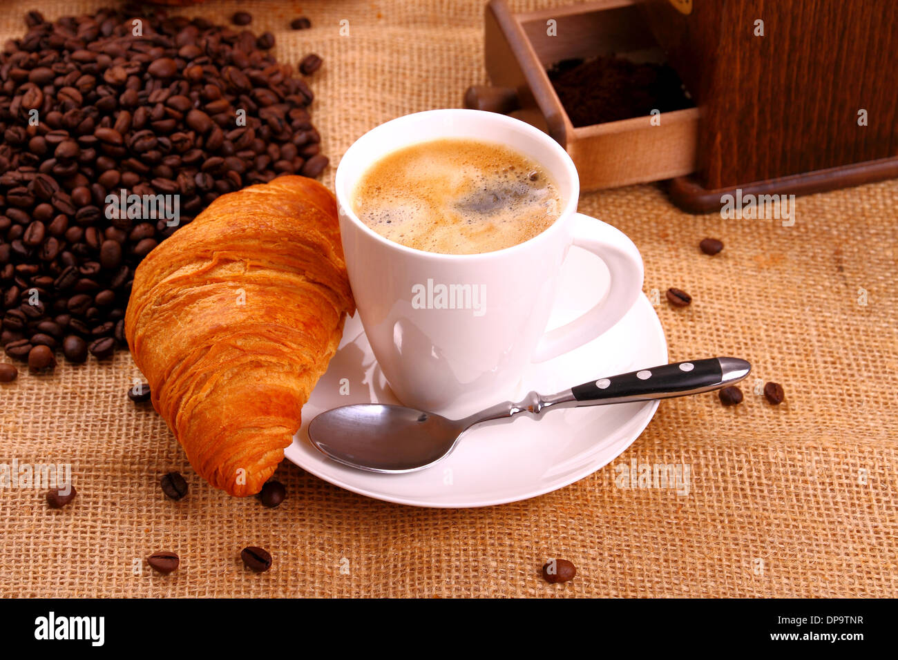 Coffee in white cup and croissant, close up - Stock Image