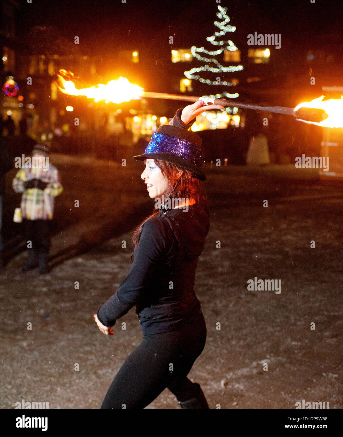 A fire spinner performs in Whistler's Olympic Plaza as part of the Family Apres Ski events.  Whistler BC, Canada. - Stock Image