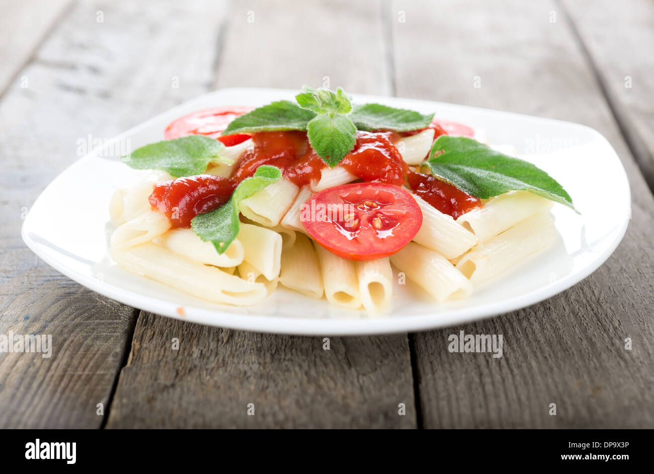 Pasta with vegetables on a wooden table - Stock Image