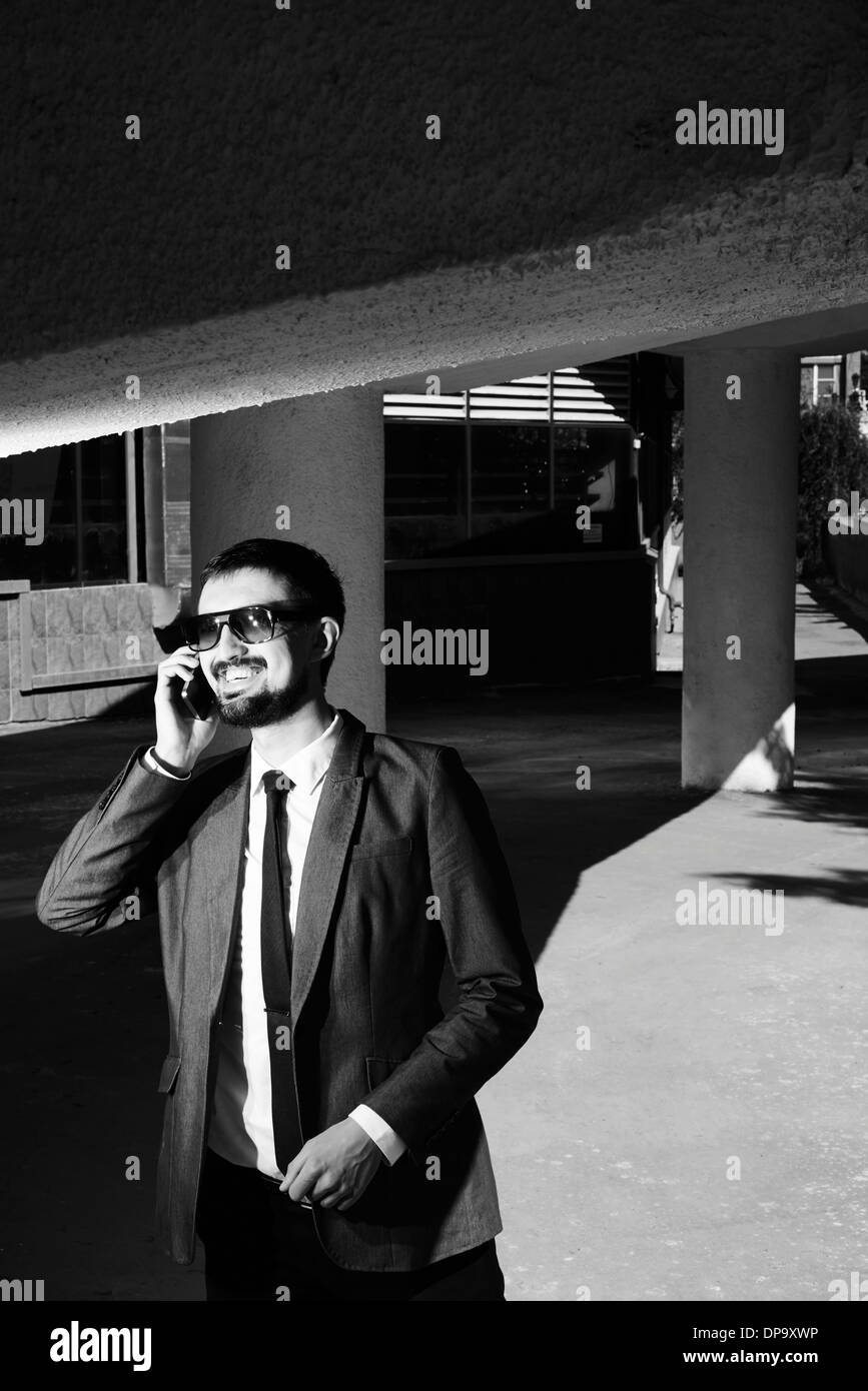 Black and white image of a smiling businessman speaking on the phone