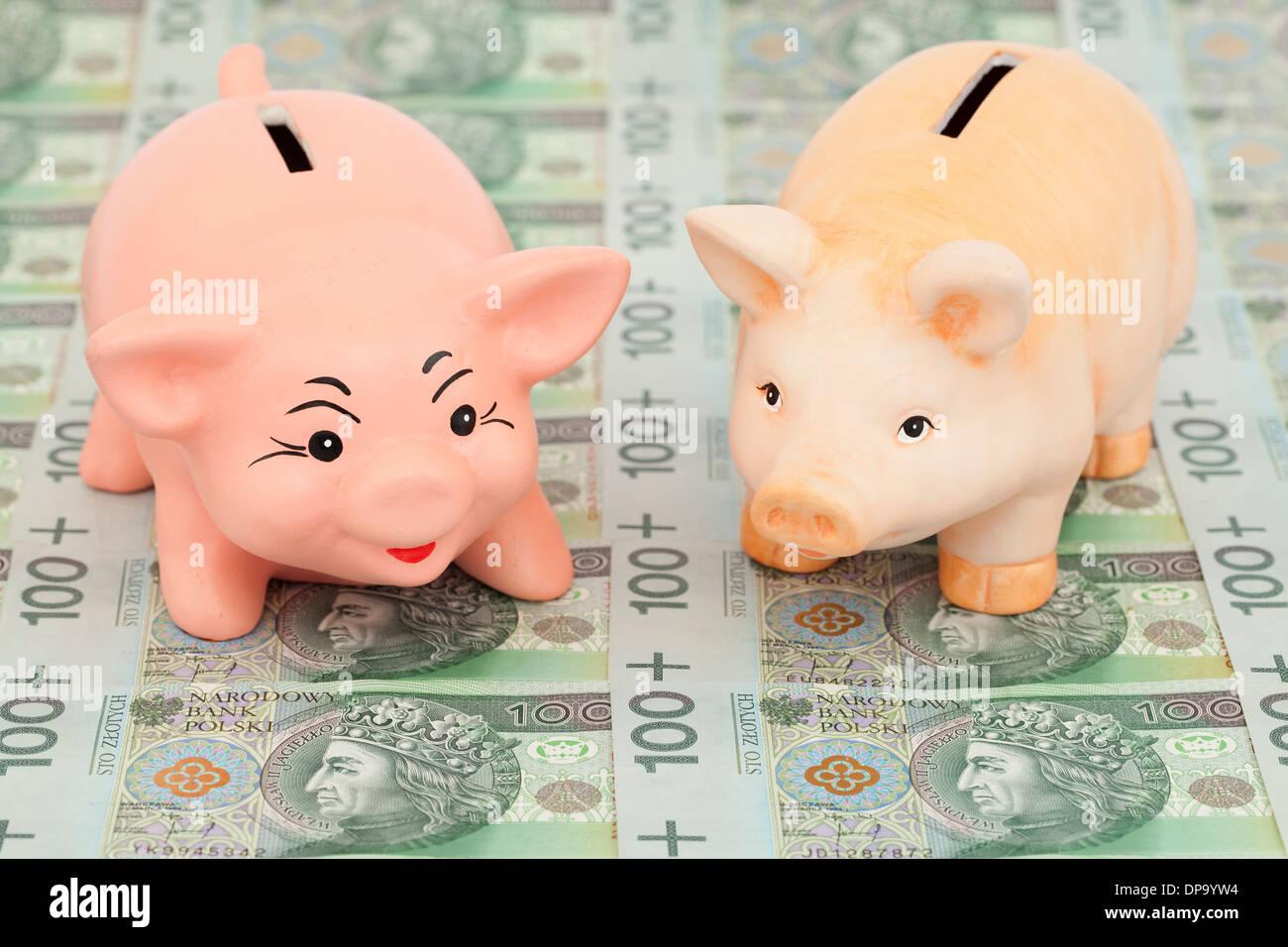 two piggy on polish money as background - Stock Image