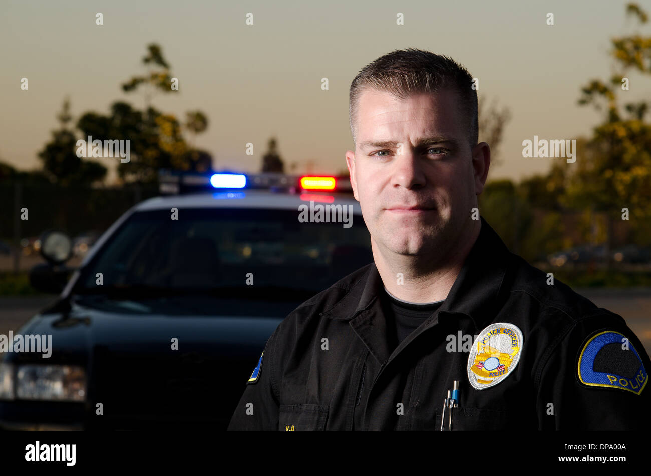 A serious looking police officer standing in his front of his patrol car. - Stock Image