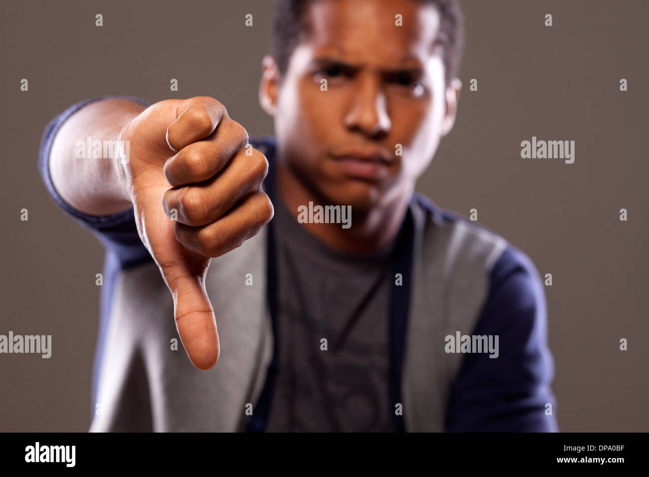 scowling dark young man showing thumb down - Stock Image