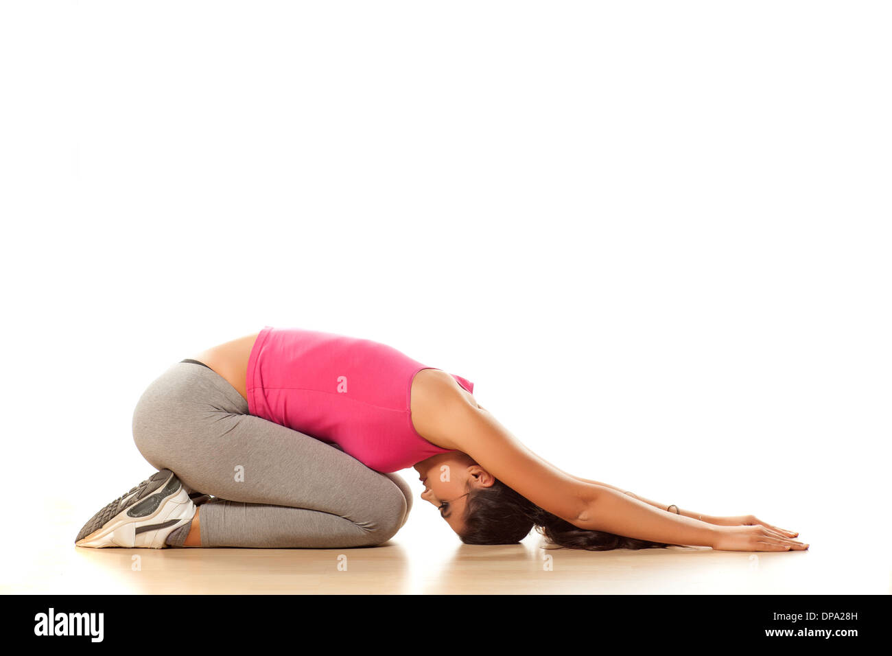 pretty girl shows yoga element fetal position for relaxation - Stock Image
