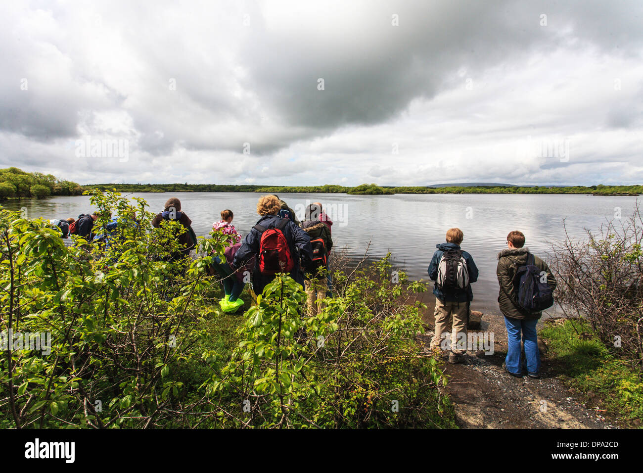 A group of walkers overlooking a lake under grey cloudy skies at the Burren National Park, County Clare, Ireland, - Stock Image