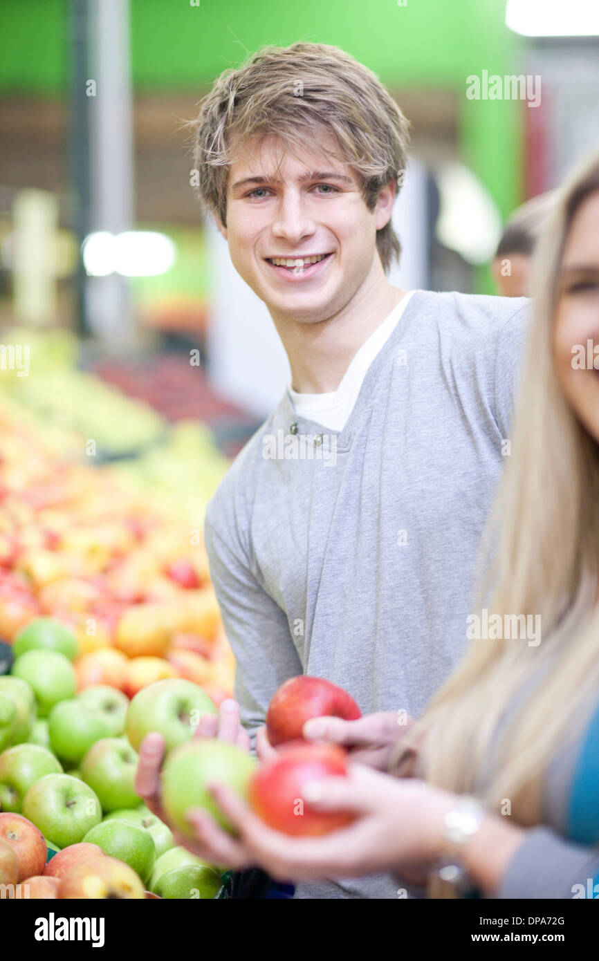 Young couple with apples in indoor market - Stock Image