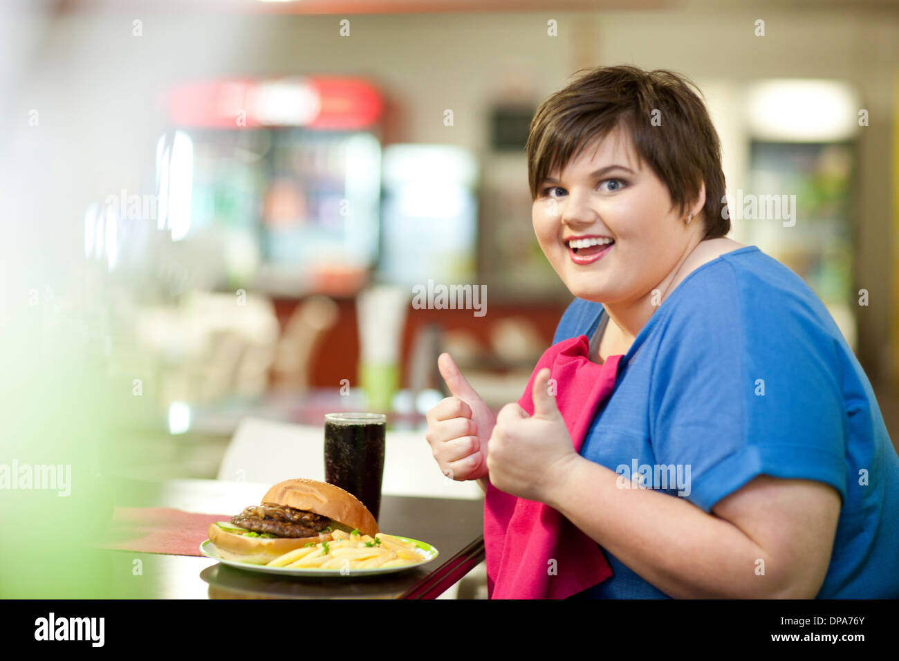 Young woman in cafe with unhealthy meal - Stock Image