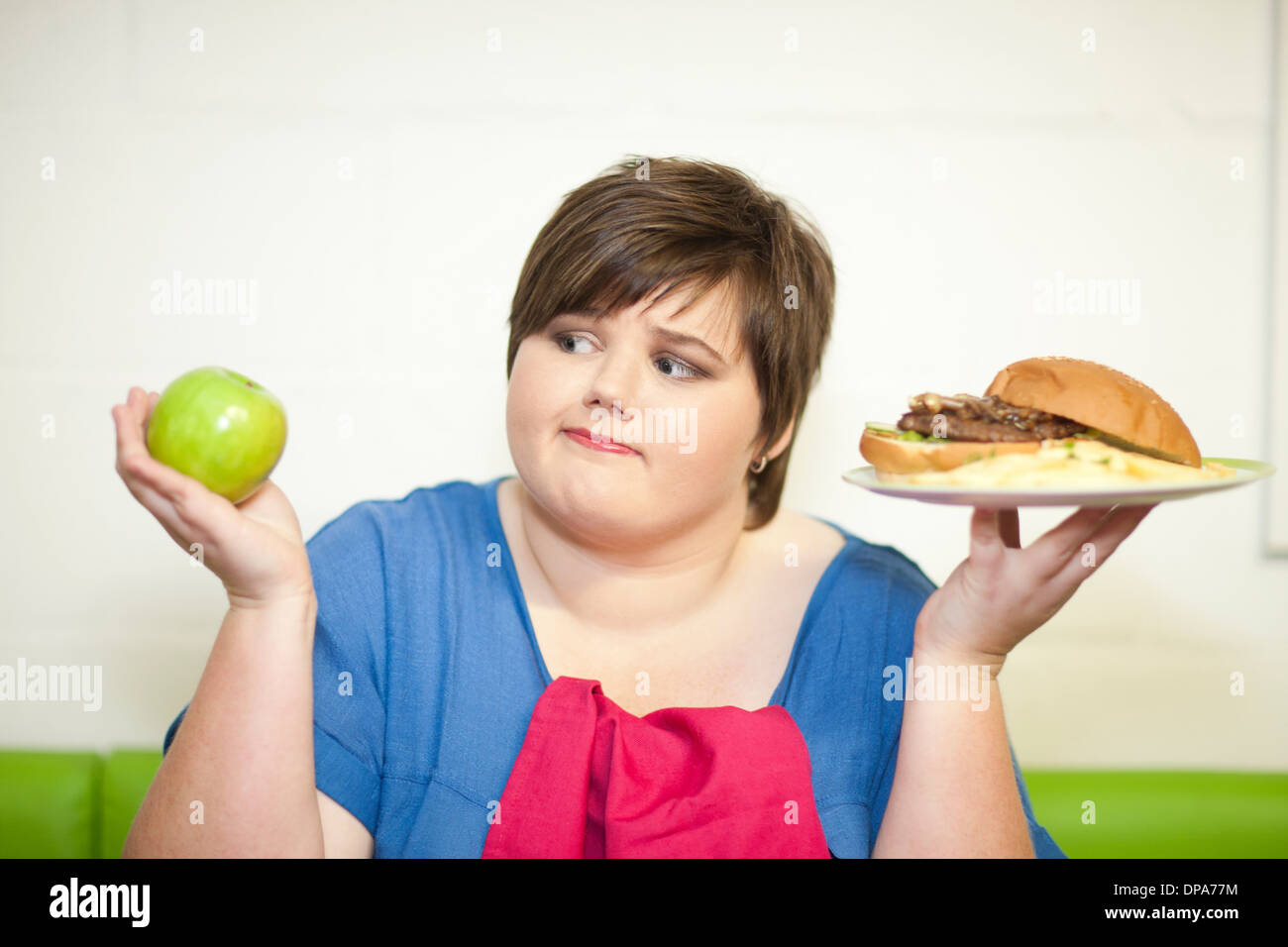 Young woman choosing between an apple and a burger - Stock Image