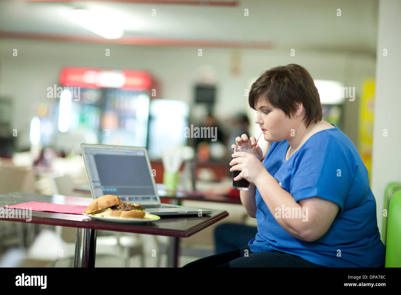 Young woman drinking coke in cafe - Stock Image