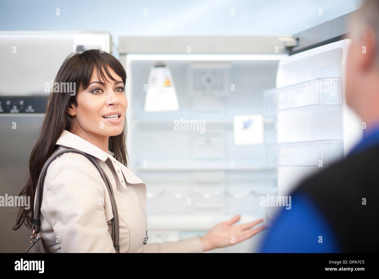 Woman looking at fridge in showroom - Stock Image