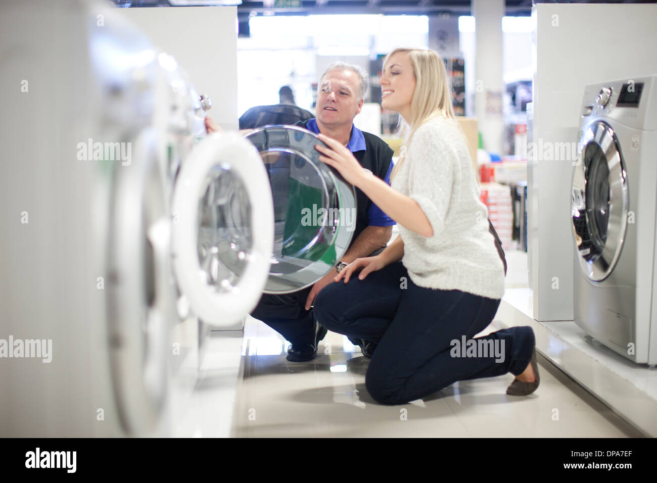Young woman and salesman looking at washing machines in showroom - Stock Image