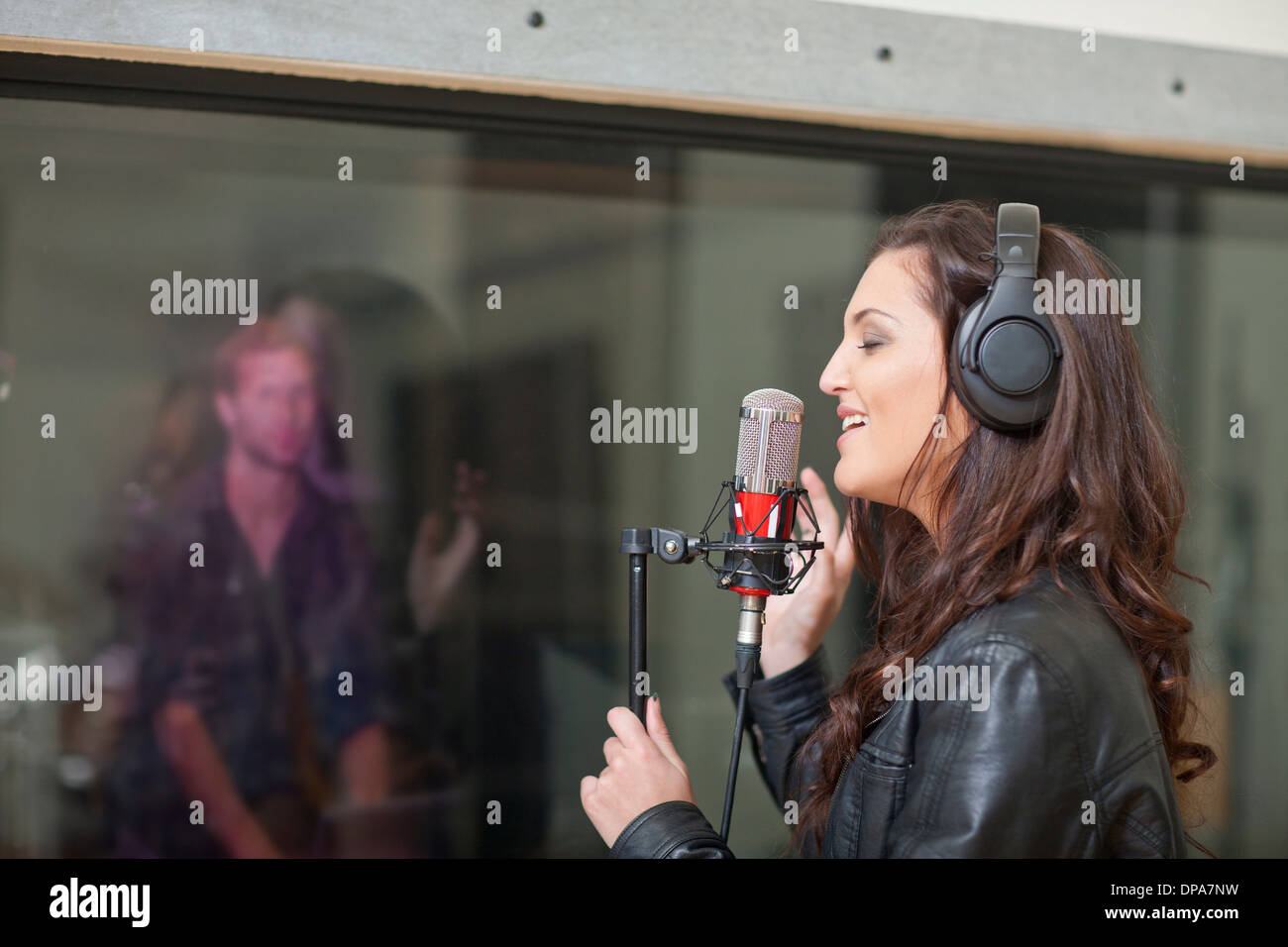 Young female singer in recording studio - Stock Image