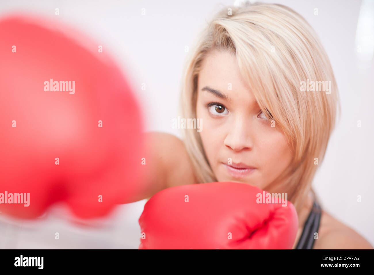 Portrait of young woman wearing boxing gloves - Stock Image