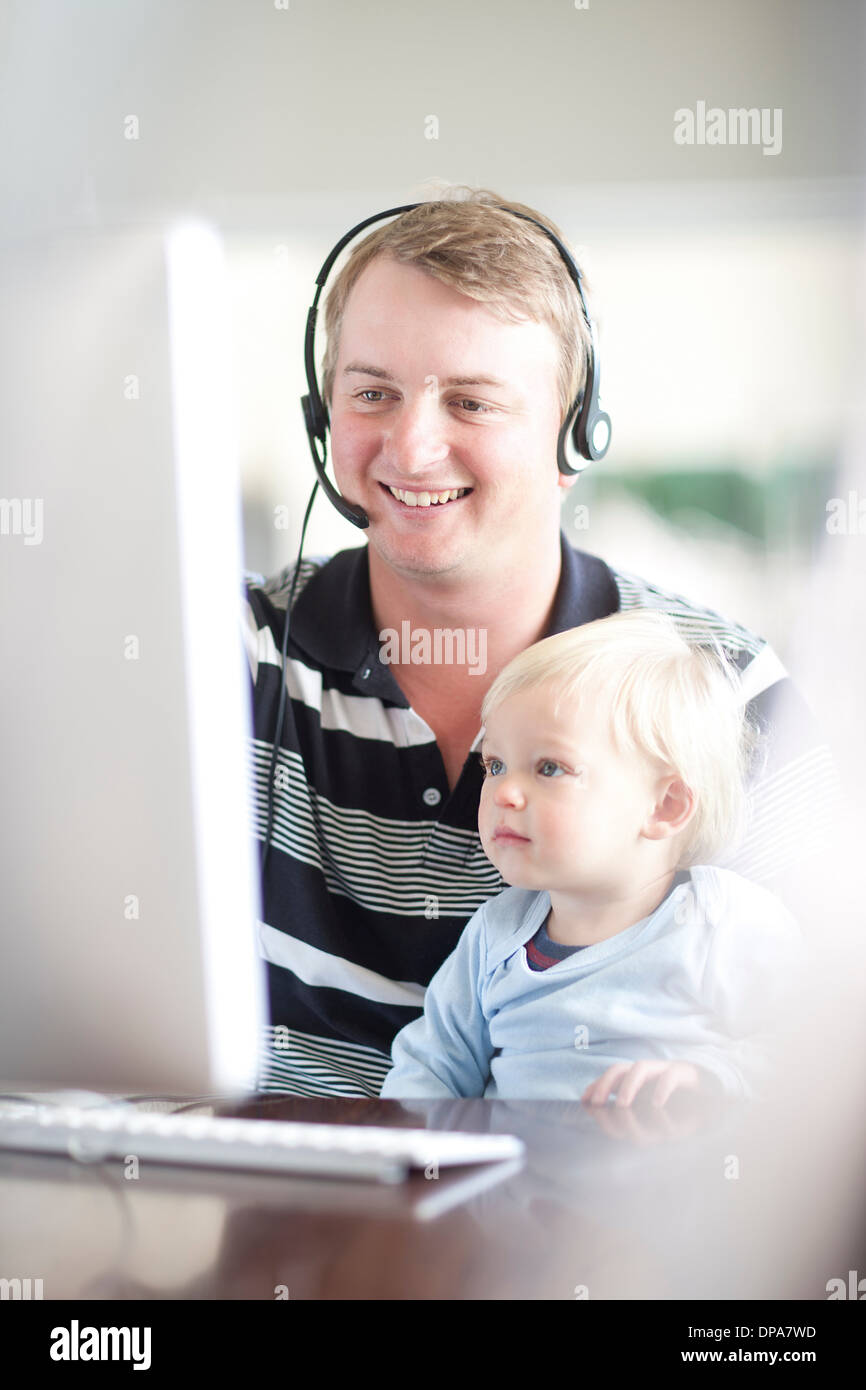 Father with baby boy using computer - Stock Image