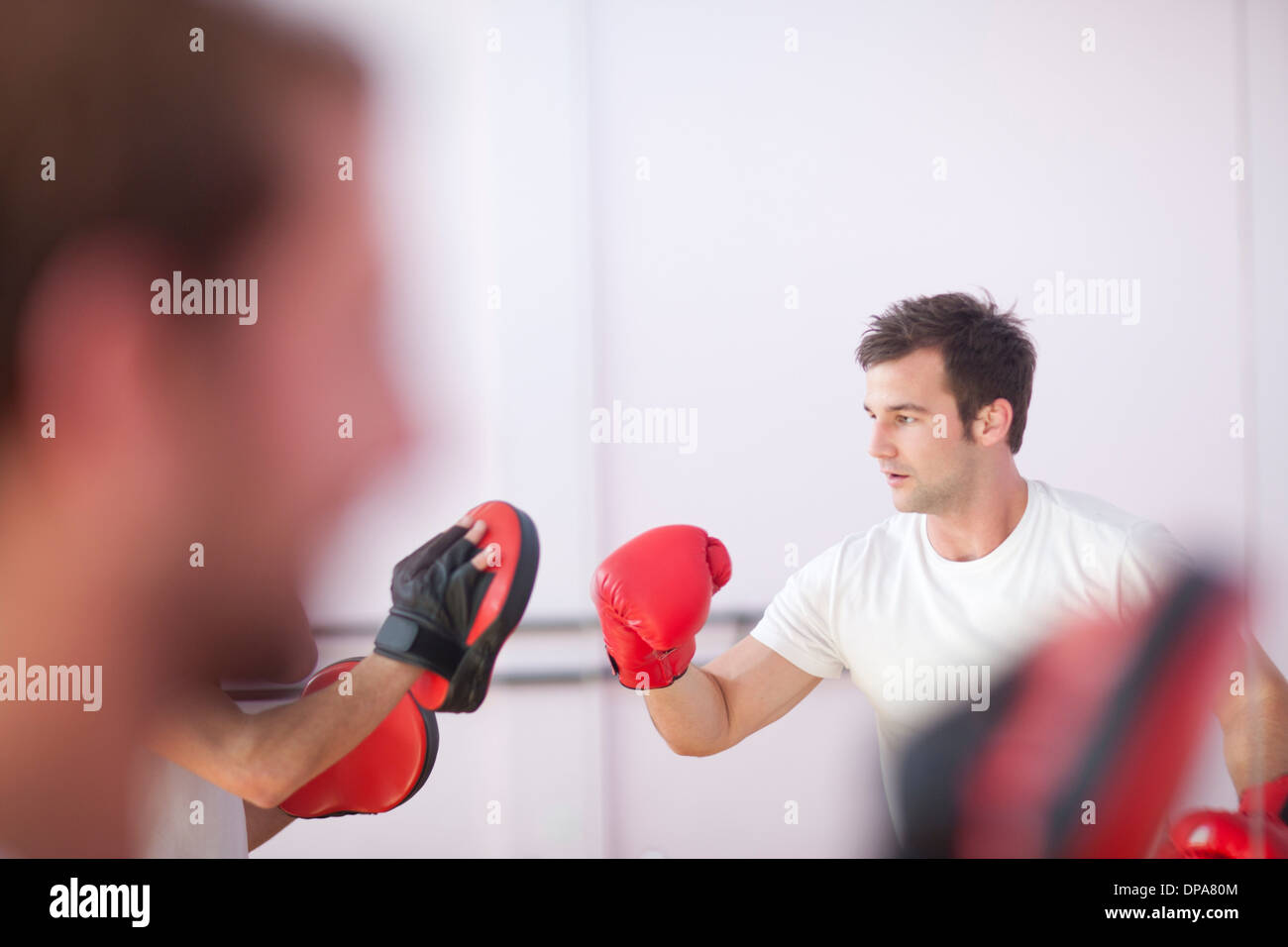 Young man and trainer boxing in sports hall - Stock Image