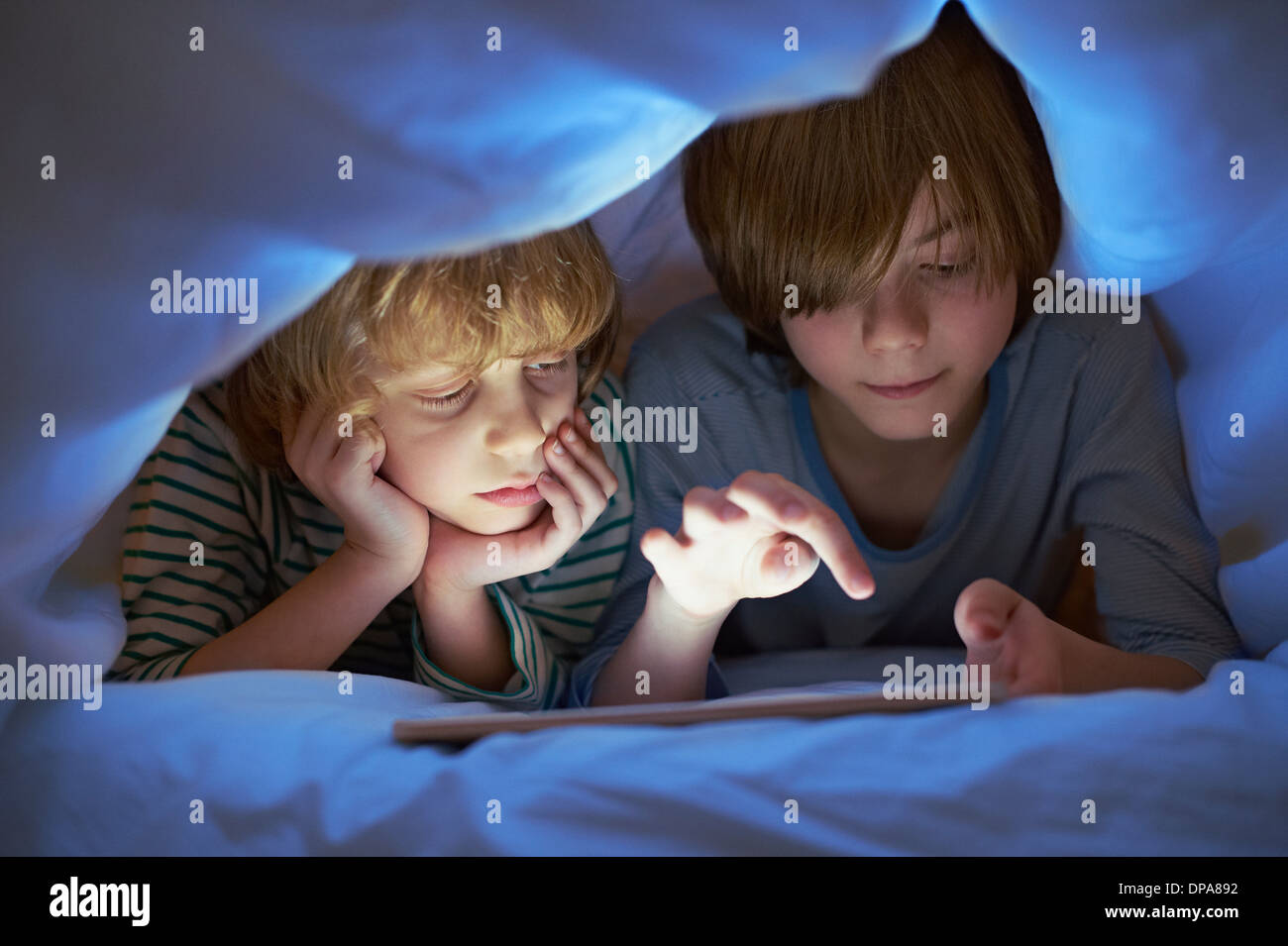 Brothers underneath duvet using digital tablet - Stock Image