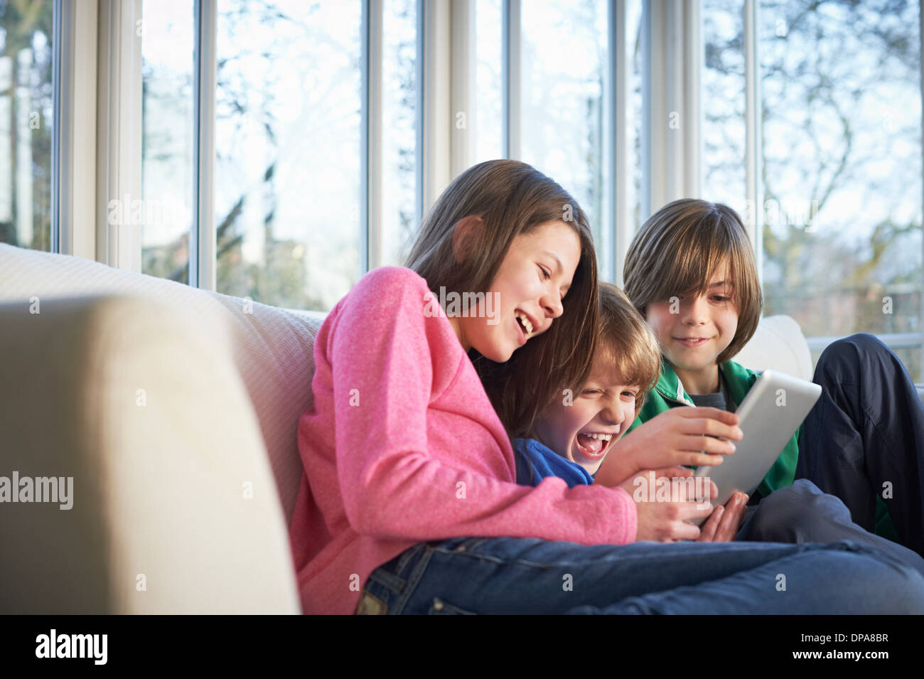 Siblings using digital tablet together Stock Photo