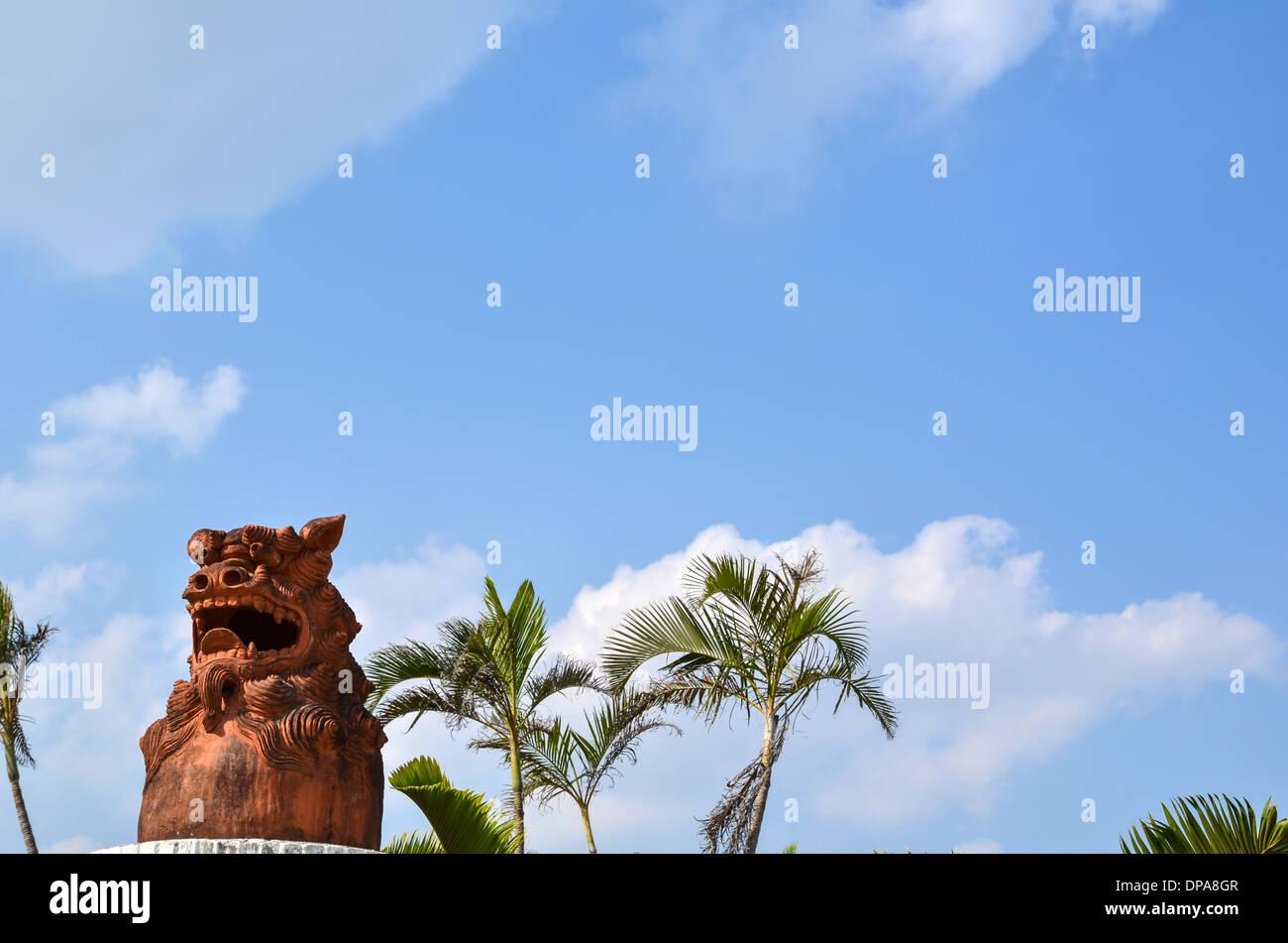 Okinawan shisa, doglion, at palm trees at the island Okinawa in japan - Stock Image
