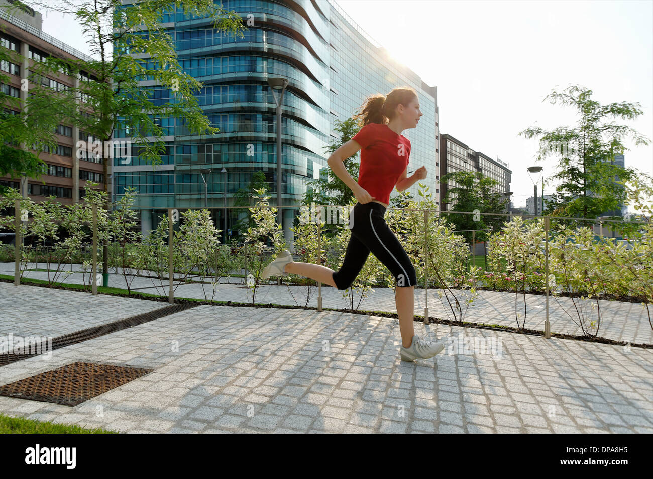 Young woman running past office buildings - Stock Image