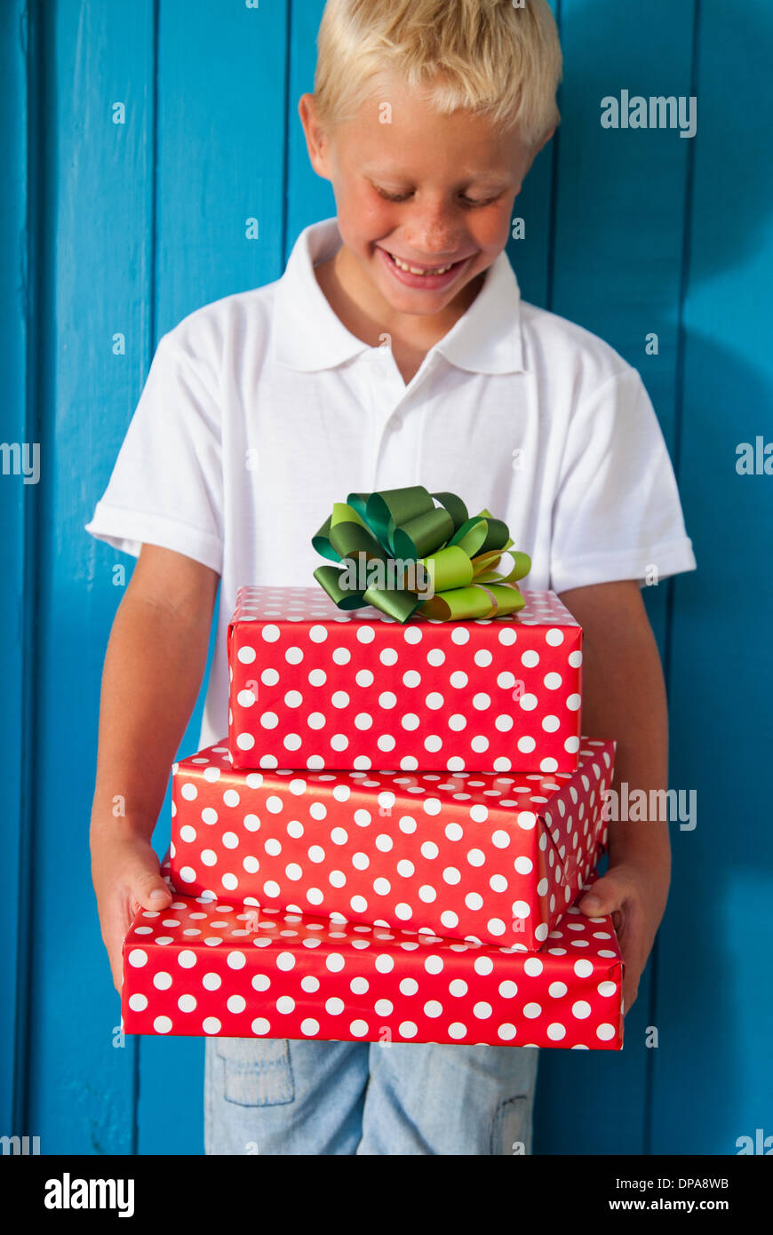 Boy looking down at gifts - Stock Image
