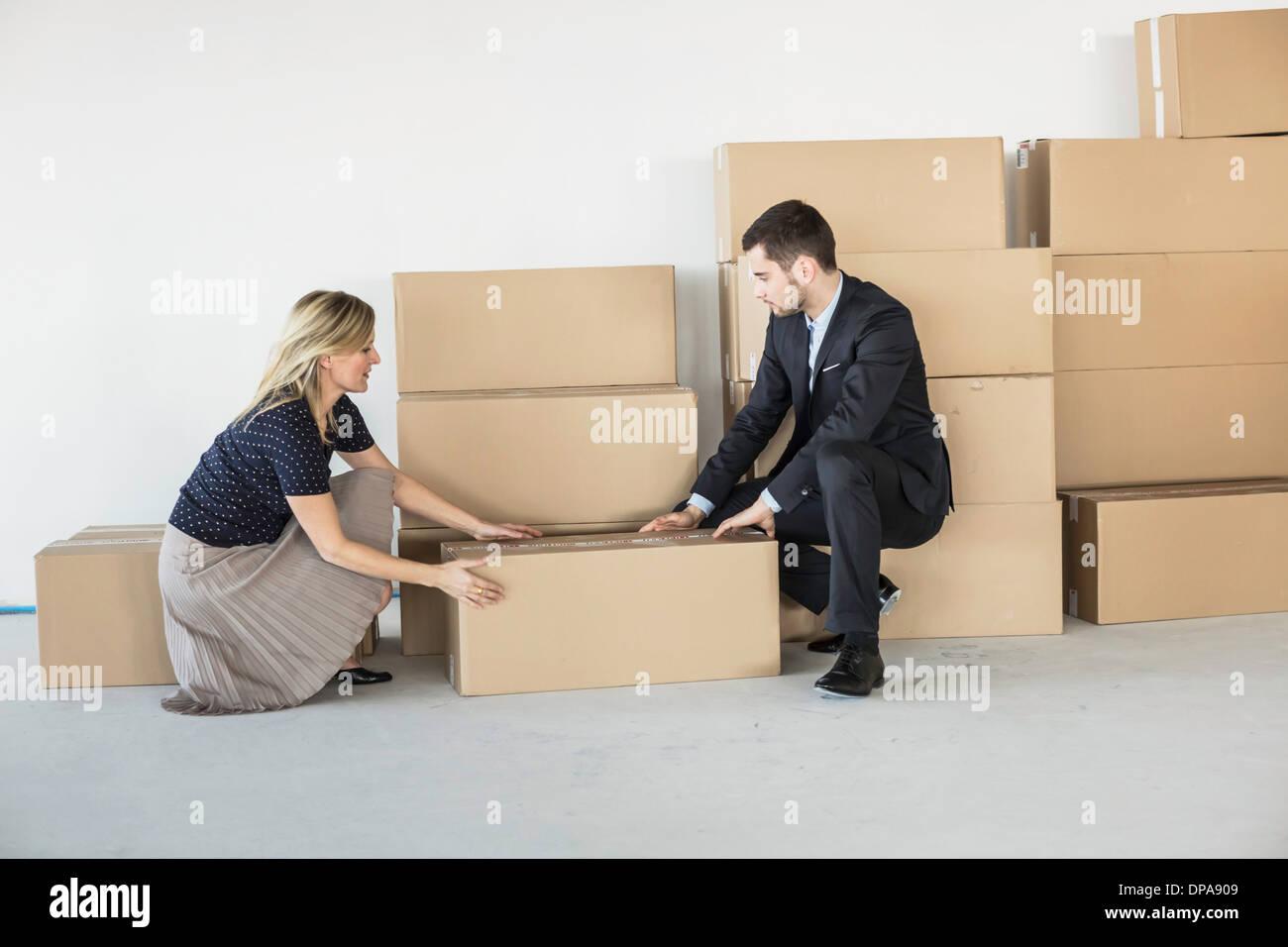 Businessman and -woman lifting cardboard box - Stock Image